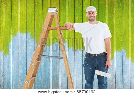 Happy man with paint roller standing by ladder against wooden planks