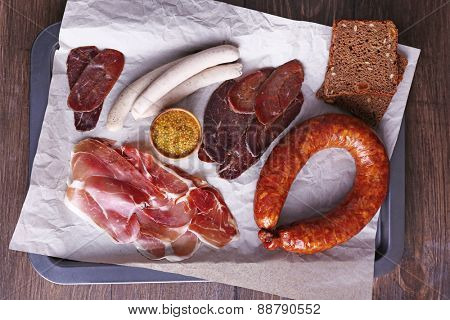 Assortment of deli meats on parchment on wooden table background