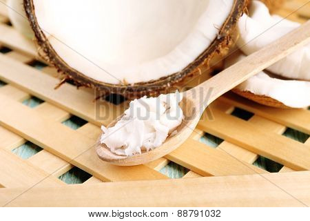 Fresh coconut flesh in wooden spoon on wooden grid background