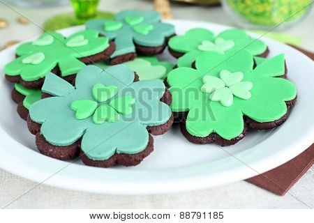 cookies in shape of clover leaf for St Patrick Day on plate on table close up
