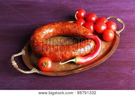 Smoked sausage with cherry tomatoes and chili pepper on metal tray on color wooden table background