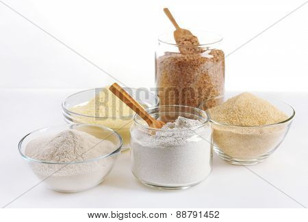 Different types of flour in bowls isolated on white