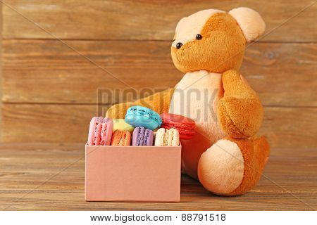Tasty colorful macaroons in present box near teddy bear and female hand on rustic wooden planks background