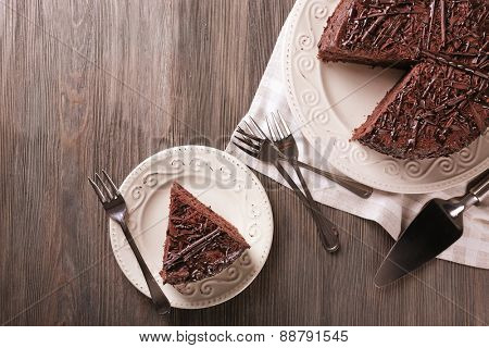 Sliced delicious chocolate cake with cutlery on wooden table background