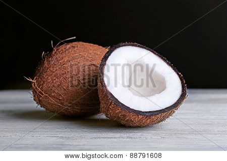 Coconut on wooden table, black background