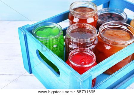 Homemade jars of fruits jam in crate on wooden table and color wall background