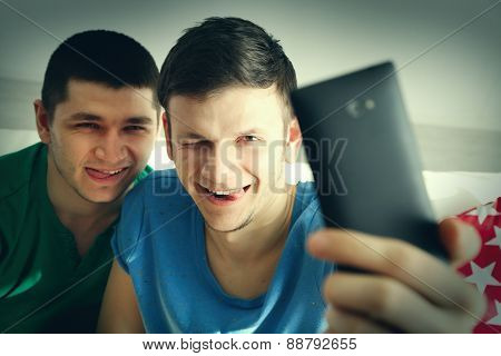 Two handsome young men sitting on sofa and making photo on mobile phone