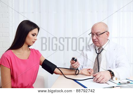 Professional doctor measuring blood pressure in his office on white curtain background
