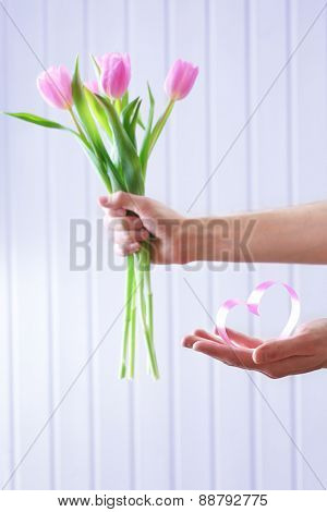 Hands holding beautiful pink tulips and decorative heart on wooden background