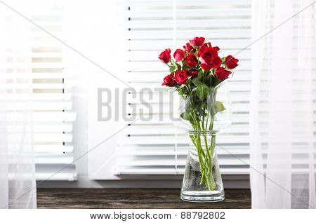 Red roses in glass vase on windowsill background