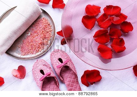 Spa bowl with water, rose petals, towel and slippers on light background. Concept of pedicure or natural spa treatment