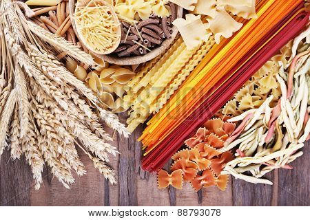 Different types of pasta with wheat on wooden table background