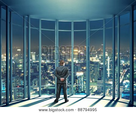 Night view of buildings and man from glass window