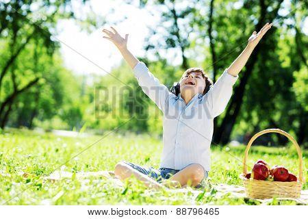 Young joyful boy in summer park wearing headphones