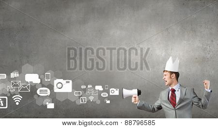 Young businessman in paper crown screaming in megaphone
