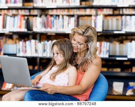 Little girl and mother with a laptop in library