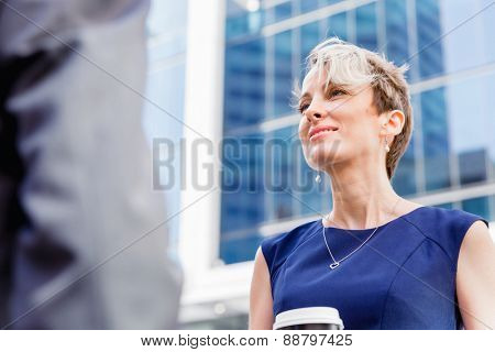Businesswoman standing and talking to her colleague outdoors