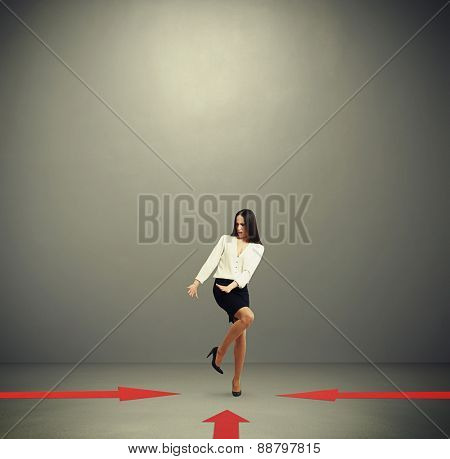 red arrows indicate at frightened woman in formal wear over dark grey background with empty copyspace overhead