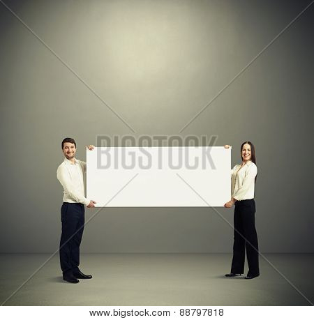 smiley woman and man holding white banner and looking at camera over grey background with empty copyspace