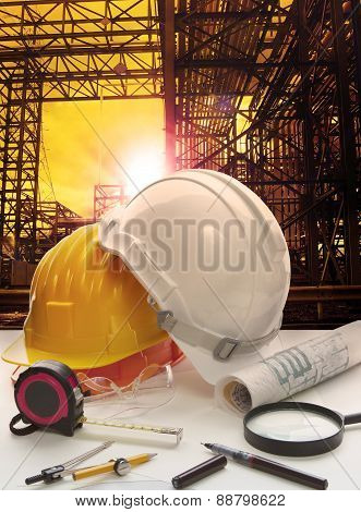 Safety Helmet On Engineer Working Table Against Pipe Line Structure In Heavy Petrochemical Industry