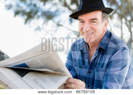 Senior gentleman reading newspaper in park