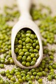 stock photo of mung beans  - Healthy green vegetarian raw mung bean seeds in wooden spoon on vintage textile background - JPG