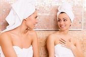 picture of sauna woman  - Two beautiful young women wrapped in towel talking to each other and smiling while relaxing in sauna