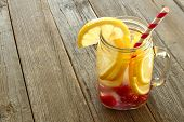 pic of masonic  - Nutritious detox water with lemon and raspberries in a mason jar against a wood background
