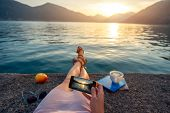 stock photo of lie  - Woman holding phone lying on the pier at beautiful sunset - JPG
