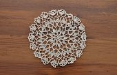 picture of doilies  - Colorful and crisp image of lace doily on dark wood - JPG