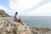 stock photo of youg  - Teenager couple hugging and looking at horizon on a cliff - JPG
