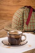 stock photo of private detective  - Coffee cup paper sheets and detective hat on old Wooden table - JPG