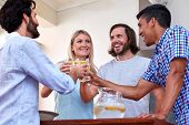 image of gathering  - young cheerful friends toasting indoors at gathering - JPG
