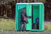 pic of porta-potties  - Girl at a portable toilets at an outdoor in the park - JPG