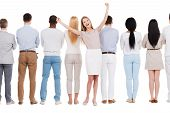 picture of positive  - Rear view of group of people standing in a row and against white background while one woman standing face to camera and expressing positivity - JPG