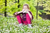 foto of blowing nose  - Little girl with allergy symptom blowing nose - JPG