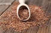 stock photo of flax plant  - Vegetarian organic nutrition flax seeds with omega fat in spoon on vintage wooden background - JPG