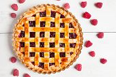picture of grease  - Tasty homemade raw raspberry pie greased with egg yolk with jam on white rustic kithen table background - JPG