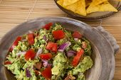 stock photo of pottery  - Guacamole and corn chips served in a pottery dish on a bamboo mat - JPG
