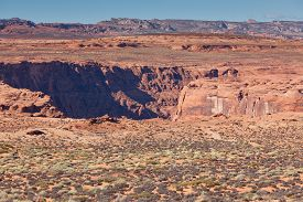 picture of enormous  - Looking down at tourist standing on the edge of Glen Canyon at Horseshoe Bend gives the perspective of the enormity of the canyon - JPG
