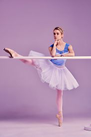 picture of ballet barre  - classic ballet dancer in white tutu posing on one leg at ballet barre on a lilac background - JPG