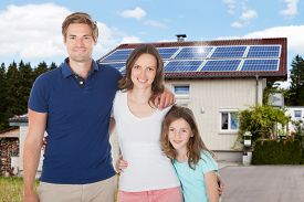 foto of in front  - Family Standing In Front House With Solar Panel On Roof - JPG