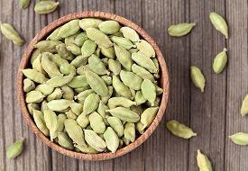 foto of cardamom  - Green cardamom ayurveda plant aroma spice in a wooden bowl on vintage background - JPG