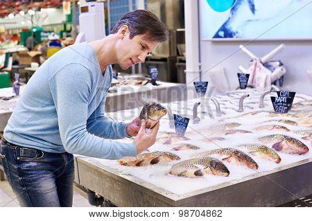 Man Chooses Carp Fish In Supermarket