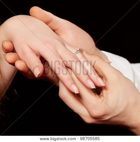 Closeup of man placing engagement ring in woman's finger