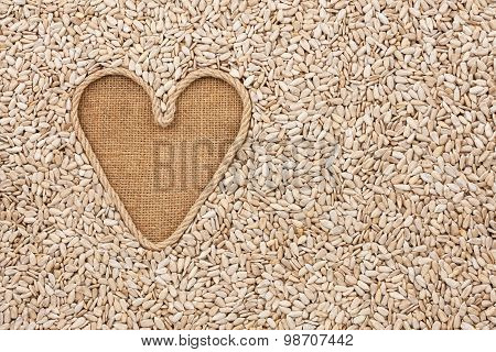 Symbolic Heart Made Of Rope Lies On Sackcloth And Sunflower Seeds