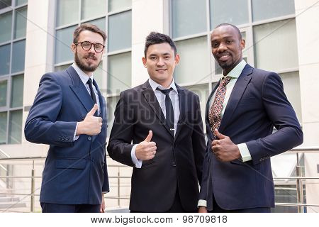 Portrait of business team holding their thumbs up