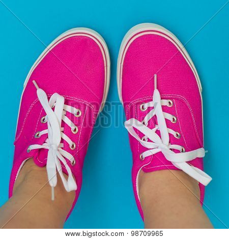 Legs In Pink Sneakers On Blue Background
