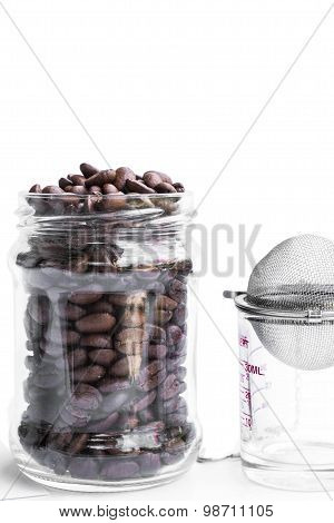 roasted coffee beans in retro glass jar with coffee shot glass and strainer