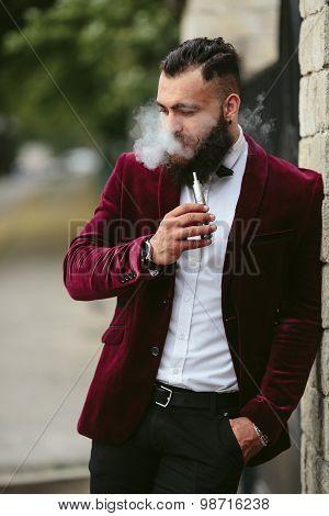 rich man with a beard smokes electronic cigarette